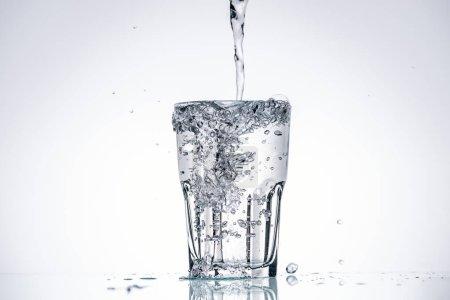 Photo pour De l'eau coulant en plein verre sur fond blanc avec rétro-éclairage et éclaboussures - image libre de droit