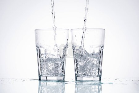 Photo for Water pouring in glasses on white background with backlit - Royalty Free Image