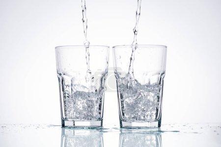 Photo pour L'eau versant dans des verres sur fond blanc avec rétroéclairage - image libre de droit