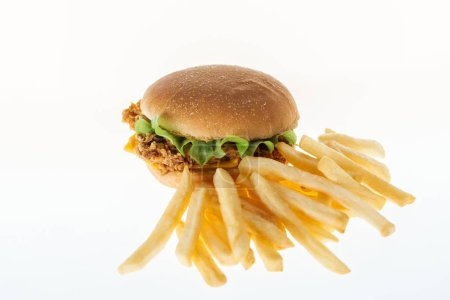 tasty unhealthy chicken burger near french fries isolated on white
