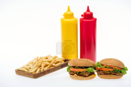 Photo for Chicken burgers near french fries and bottles with mustard and ketchup isolated on white - Royalty Free Image