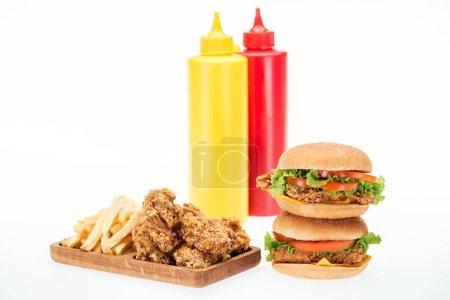 Photo pour Pépites de poulet croustillantes, hamburgers et frites près de bouteilles de ketchup et moutarde isolées sur blanc - image libre de droit