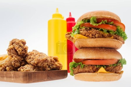 Photo for Selective focus of crispy chicken nuggets and chicken burgers near bottles with ketchup and mustard isolated on white - Royalty Free Image