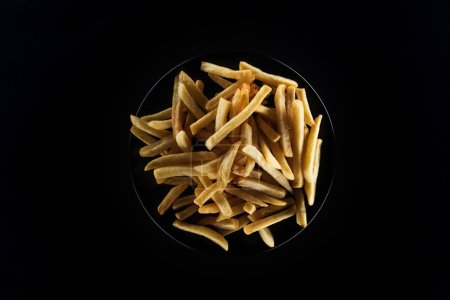 Photo for Top view of tasty french fries on plate isolated on black - Royalty Free Image