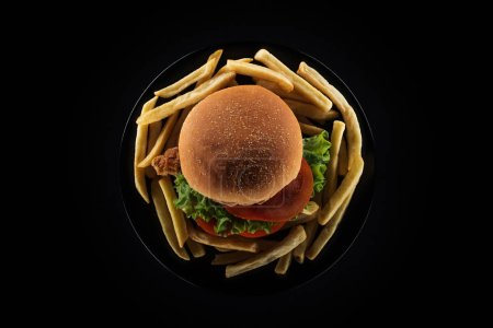 Photo for Top view of tasty french fries and chicken burger on plate isolated on black - Royalty Free Image