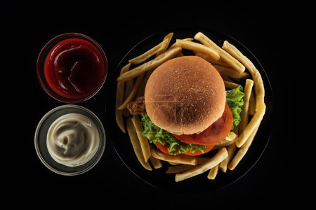 Photo for Top view of tasty french fries and chicken burger near mayonnaise and ketchup isolated on black - Royalty Free Image