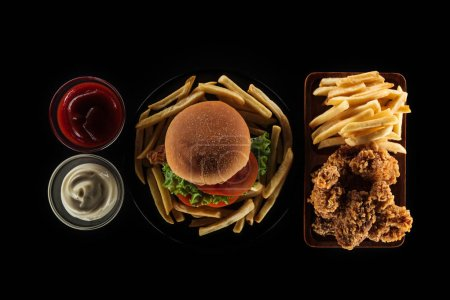 Photo for Top view of tasty unhealthy meal isolated on black - Royalty Free Image