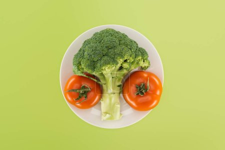 Photo for Top view of organic ripe broccoli near red tomatoes on white plate isolated on green - Royalty Free Image