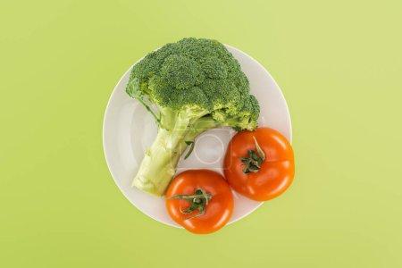 Foto de Vista superior de brócoli orgánico cerca de tomates rojos en plato blanco aislado en verde - Imagen libre de derechos