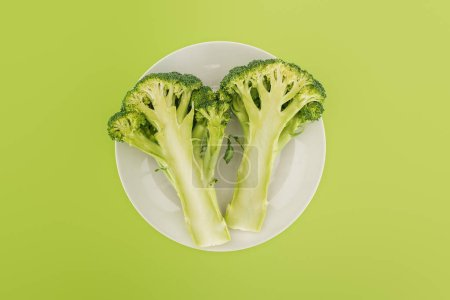 Photo for Top view of tasty organic broccoli on white plate isolated on green - Royalty Free Image