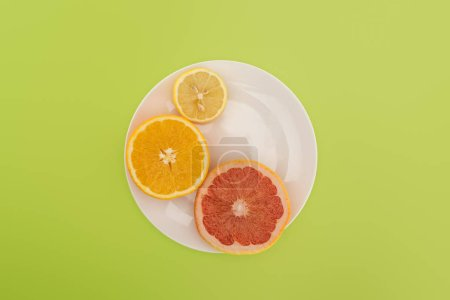 Photo for Top view of sliced orange, lemon and grapefruit on white plate isolated on green - Royalty Free Image