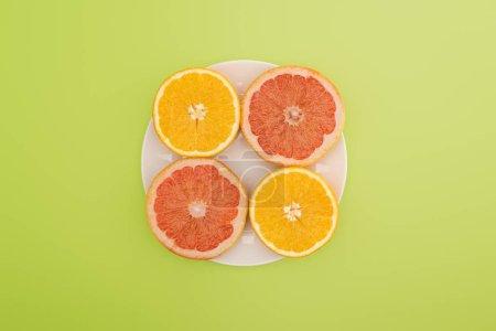 vista superior de naranjas en rodajas y pomelos en plato blanco aislado en verde