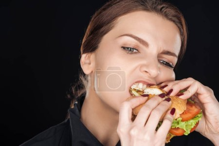 Photo for Angry woman eating tasty chicken burger isolated on black - Royalty Free Image