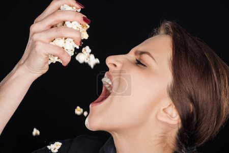 Photo for Emotional woman eating salty popcorn isolated on black - Royalty Free Image