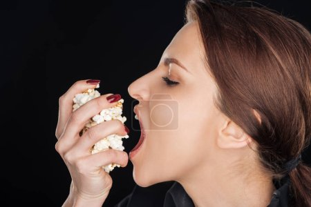 Photo for Attractive woman eating salty popcorn isolated on black - Royalty Free Image