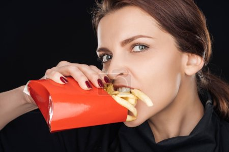 attractive woman eating salty french fries while looking at camera isolated on black