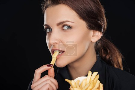 Photo for Attractive while eating tasty french fry isolated on black - Royalty Free Image