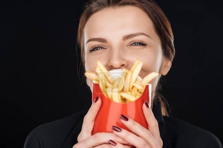 Photo for Woman covering face with french fries isolated on black - Royalty Free Image