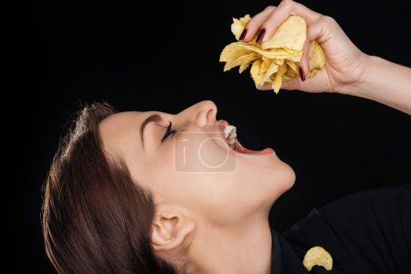 Photo for Beautiful woman eating crispy chips isolated on black - Royalty Free Image