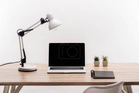Photo pour Lieu de travail moderne avec ordinateur portable avec écran blanc, plantes, lampe et portable isolé sur blanc - image libre de droit