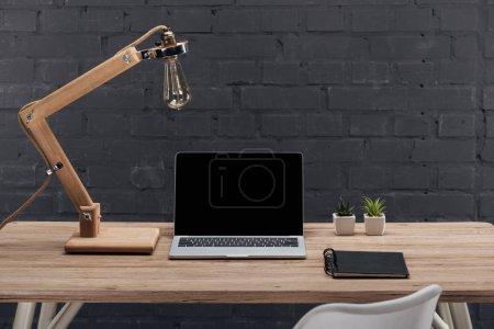 Foto de Trabajo moderno con ordenador portátil con pantalla en blanco, las plantas, lámpara y cuaderno en la mesa de madera - Imagen libre de derechos