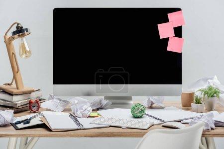 Foto de Moderno lugar de trabajo con computadoras, papelería y arrugados papeles en el escritorio de madera aislado en gris - Imagen libre de derechos