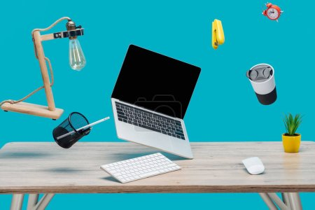 Photo for Laptop with blank screen and stationery levitating in air at workplace isolated on turquoise - Royalty Free Image