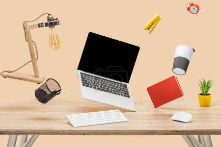 laptop with blank screen and stationery levitating in air above wooden desk isolated on beige