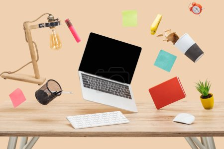 Photo for Laptop with blank screen, thermomug with coffee splash and stationery levitating in air above wooden desk isolated on beige - Royalty Free Image