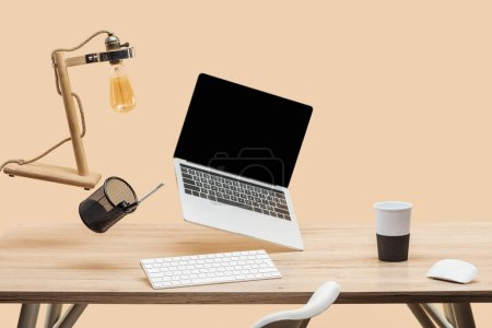 Photo pour Ordinateur portable avec écran blanc, lampe et articles de papeterie en lévitation dans l'air au-dessus de bureau en bois isolées sur beige - image libre de droit