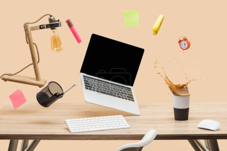 Photo for Laptop with blank screen, lamp, empty sticky notes and stationery levitating in air above workplace with thermomug with coffee splash  on table isolated on beige - Royalty Free Image