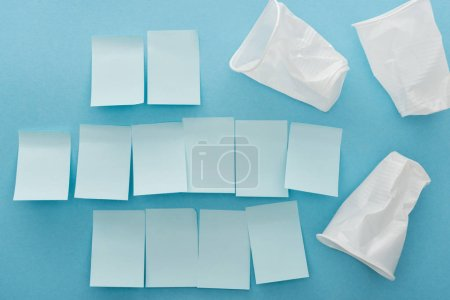 Photo for Top view of white plastic and crumpled cups and empty sticky notes on blue background - Royalty Free Image