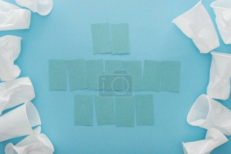 Photo for Top view of white plastic cups and blank sticky notes with copy space on blue background - Royalty Free Image