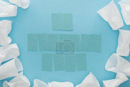Foto de Vista superior de vasos de plástico blanco y vacíos papelitos con espacio de copia sobre fondo azul - Imagen libre de derechos