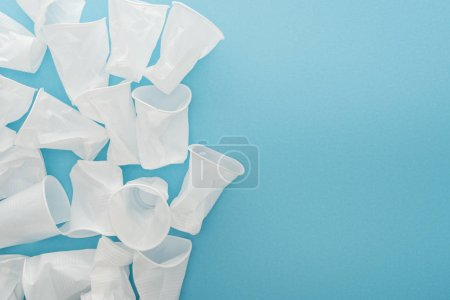 Photo for Top view of white and crumpled plastic cups on blue background with copy space - Royalty Free Image