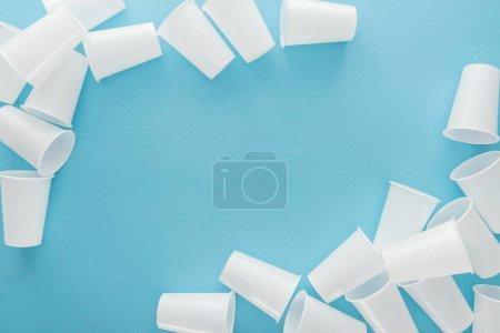 Photo pour Vue de dessus des gobelets en plastique blancs sur fond bleu avec espace copie - image libre de droit