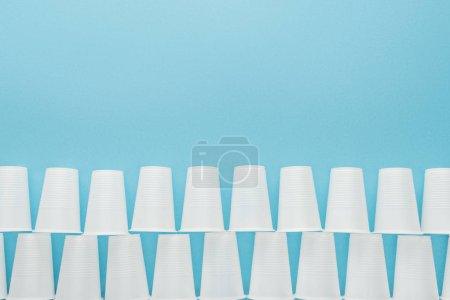 flat lay with white plastic cups isolated on blue with copy space