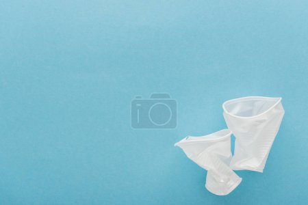 top view of white, crumpled plastic cups on blue background with copy space