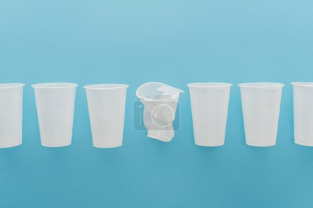 Photo for Flat lay with white plastic cups on blue background with copy space - Royalty Free Image