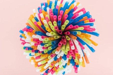 Foto de Vista superior de las pajitas de plástico coloridas y brillantes aislado en rosa - Imagen libre de derechos