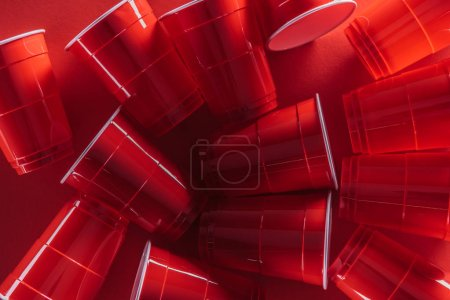 Foto de Vista superior de vasos de plástico brillantes y coloridos sobre fondo rojo - Imagen libre de derechos