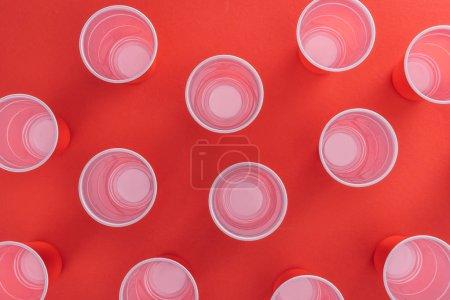 Photo pour Vue de dessus des gobelets en plastique lumineux et colorés sur fond rouge - image libre de droit