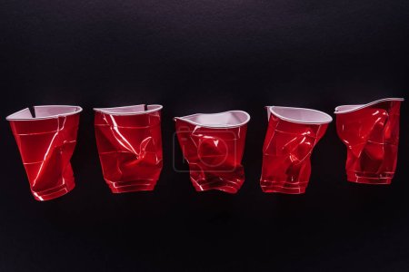 top view of bright and colorful, red plastic cups isolated on black