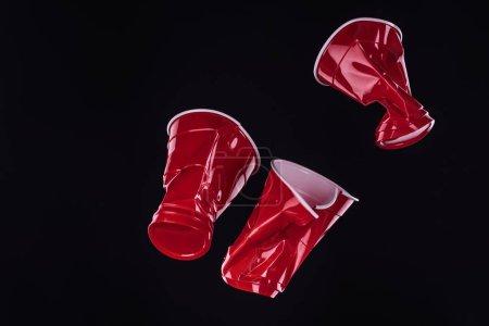 Photo pour Vue du rouge lumineux et coloré, de dessus les gobelets en plastique isolées sur fond noir avec l'espace de copie - image libre de droit