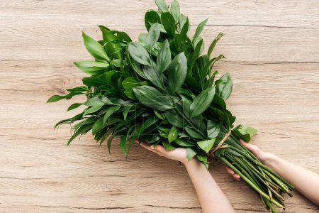 Photo for Cropped view of florist holding green bouquet on wooden surface - Royalty Free Image