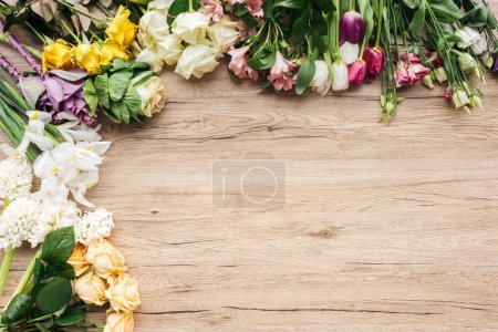 Photo for Top view of fresh colorful flowers on wooden surface - Royalty Free Image