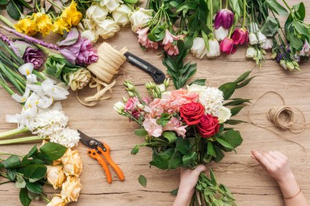 Cropped view of florist holding bouquet of fresh flowers on wooden surface