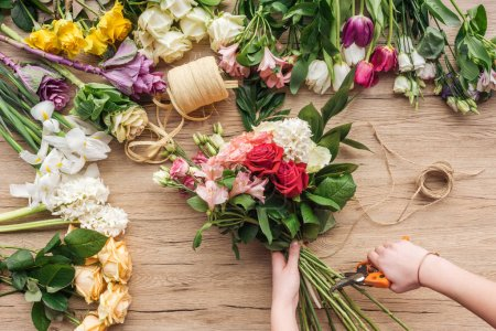 Partial view of florist holding bouquet and prunning flower stalks on wooden surface