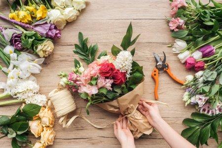Photo pour Vue recadrée du fleuriste faisant bouquet de fleurs sur la surface en bois - image libre de droit
