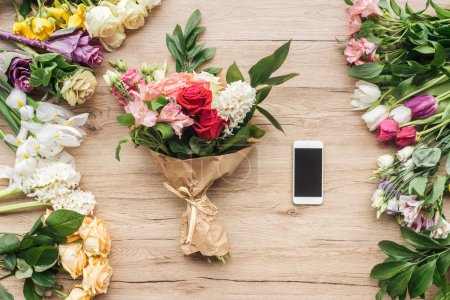 Photo for Fresh flowers and smartphone with blank screen on wooden surface - Royalty Free Image